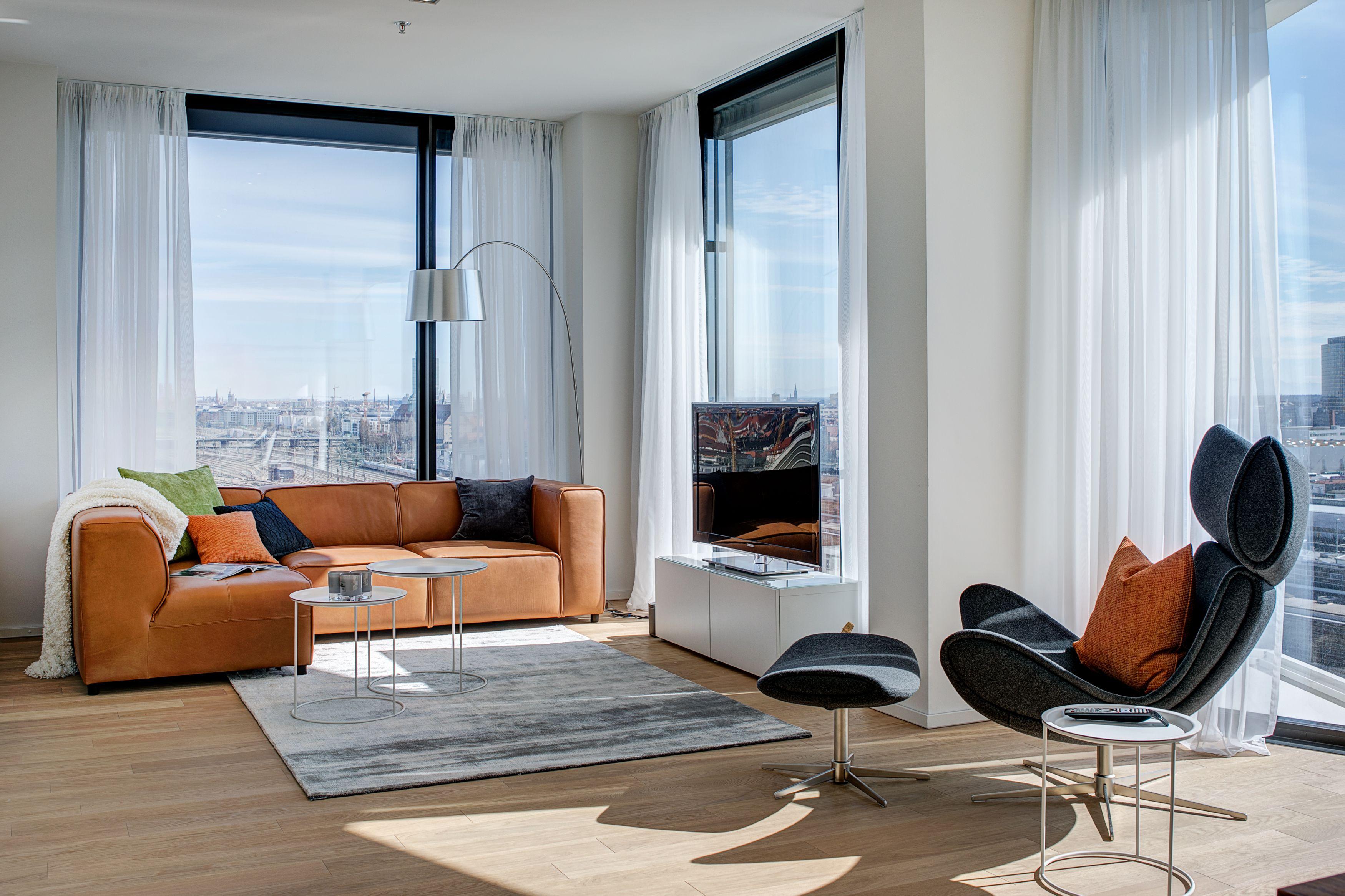 Professionell eingerichtetes Wohnzimmer mit bodentiefen Fenstern und ...