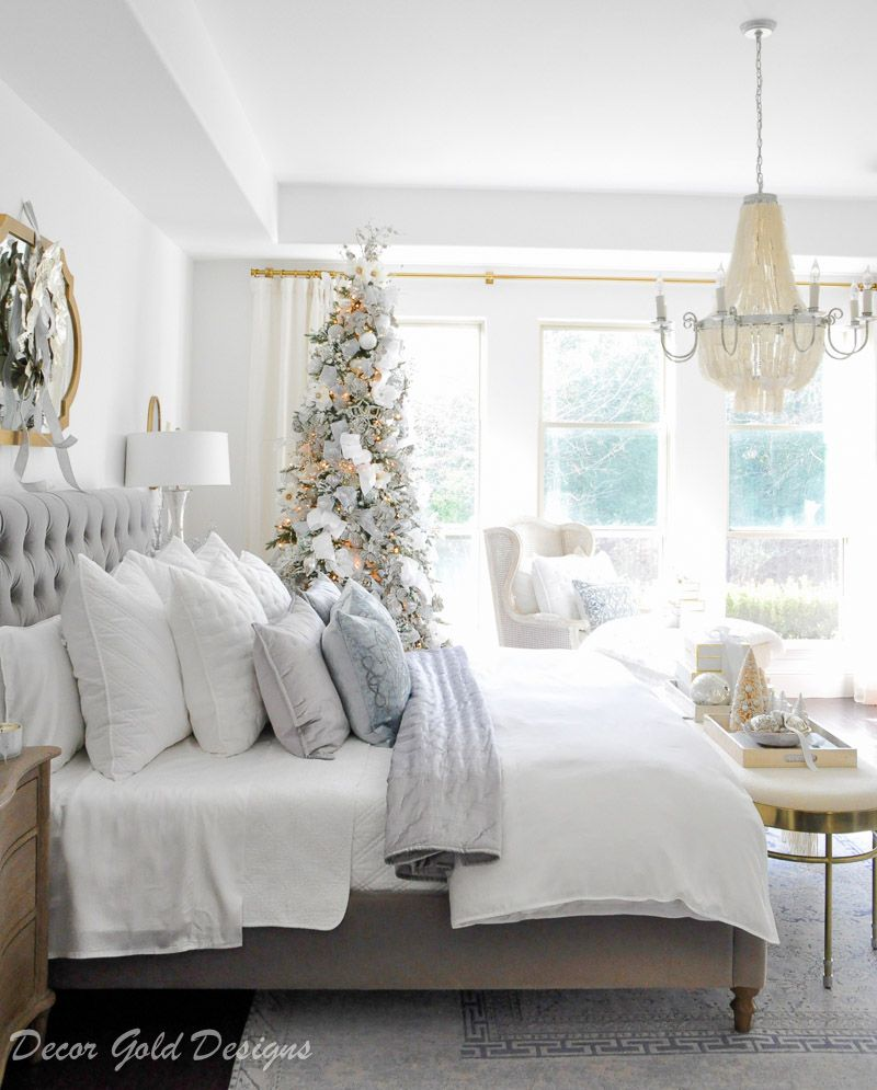 Winter white, gray and silver Christmas bedroom with beautiful gold accents. A decorated tree…
