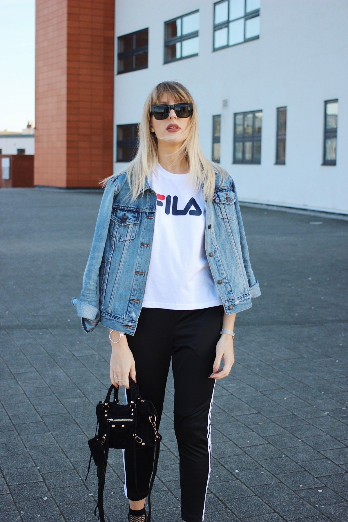 9f6cb91de8b8 styling the logo t-shirt trend street style - Fila tee, Balenciaga Bag,  Saint Laurent Sunglasses and Levi Denim Jacket Outfit inspiration