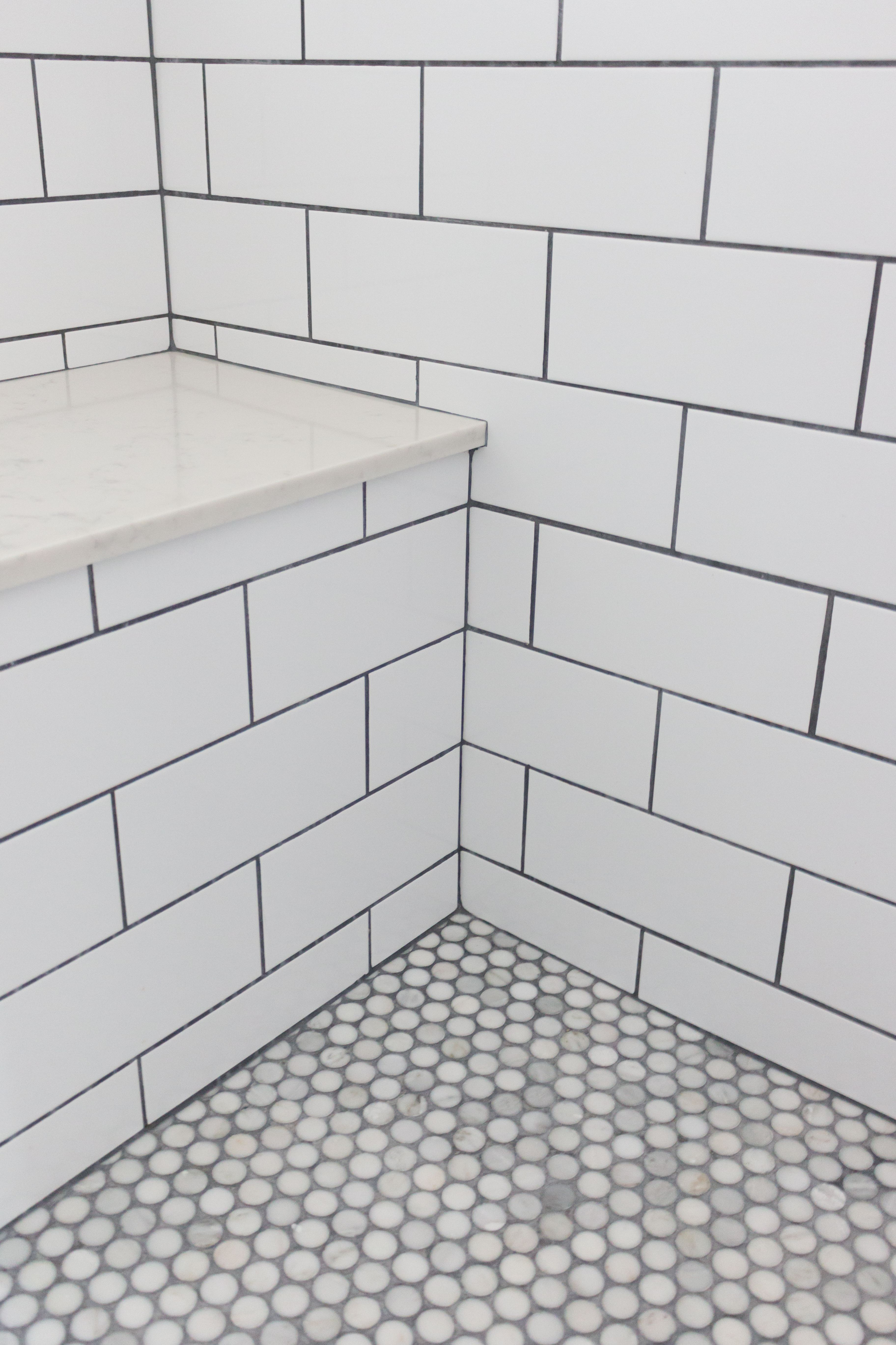 Master bathroom shower. Subway tile with grey grout, stone bench and ...