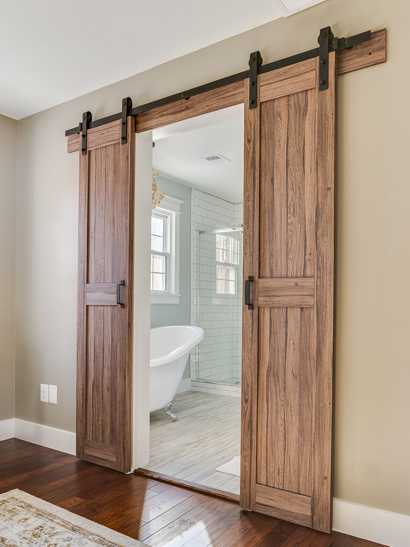 Barn doors leading into master bathroom in a modern