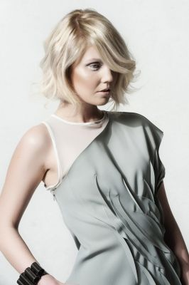 The long layered hairstyle with XL fringe combines platinum blond with gentle ivory shimmer.