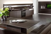 Streamlined kitchens in darker finishes, glass backsplashes, pull out faucets and LED lighting top some of the upcoming kitchen trends according to NKBA.