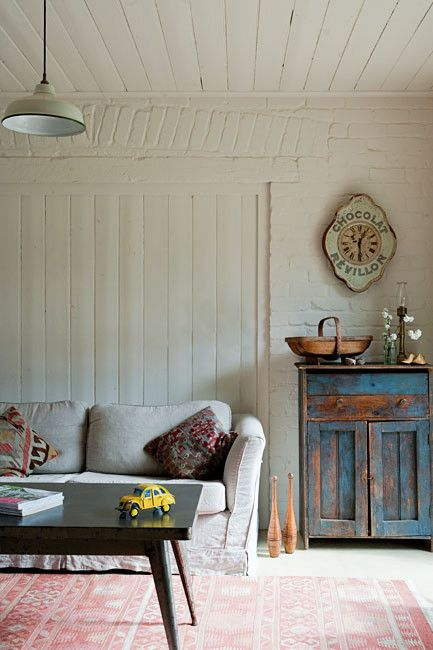 linen sofa, kilim rug and whitewashed brick and wood plank walls