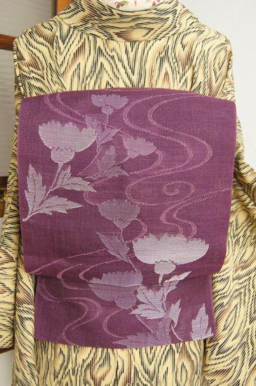 山葡萄の実のような、こっくりと深いスモークがかった愁いをおびた紅紫色に、くるりと渦を巻く涼やかな流水と、涼風にさやと揺れるようなアザミの花が織り出された、紗の夏帯です。