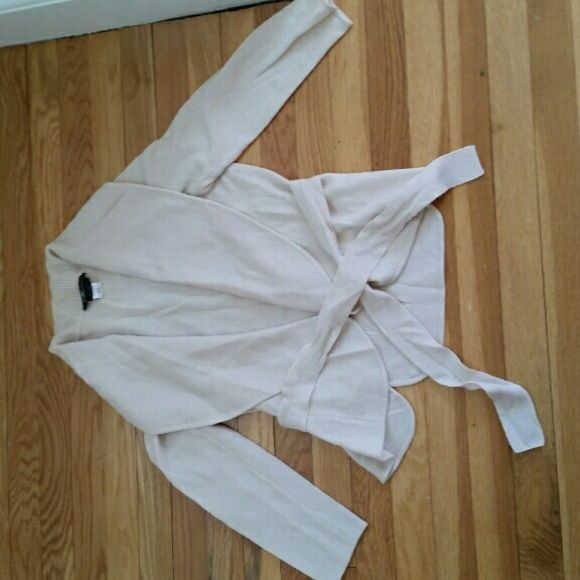 BCBG merino cream sweater size M This sweater is everything!  A super cut that is incredibly versatile,  this is a great item that can be worn to work, then transition to an evening out for dinner with girlfriends item. The sash is attached and can tie around the waist int the front or in an adorable bow in the back. A nice merino wool gives it substantial warmth without being bulky. BCBGMaxAzria Sweaters Cardigans