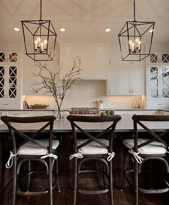 White Cabinets With X Mullions And Oversized Pendant Lighting