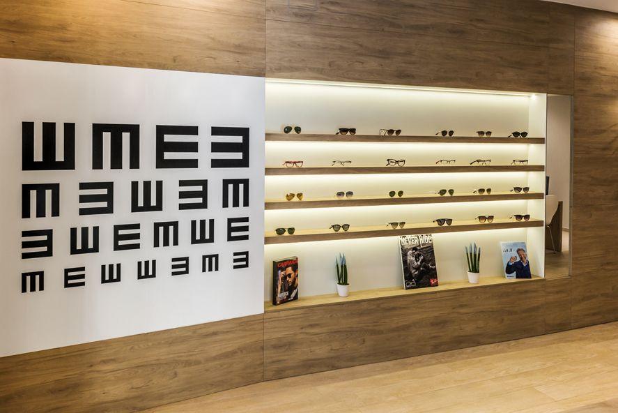Diseño de óptica. Mobiliario a medida para expositor de gafas. Estantes con iluminación led. Revestimiento y estantes en melamina  simulación roble. Gráfica de optometría como elemento decorativo y diferenciador del proyecto.