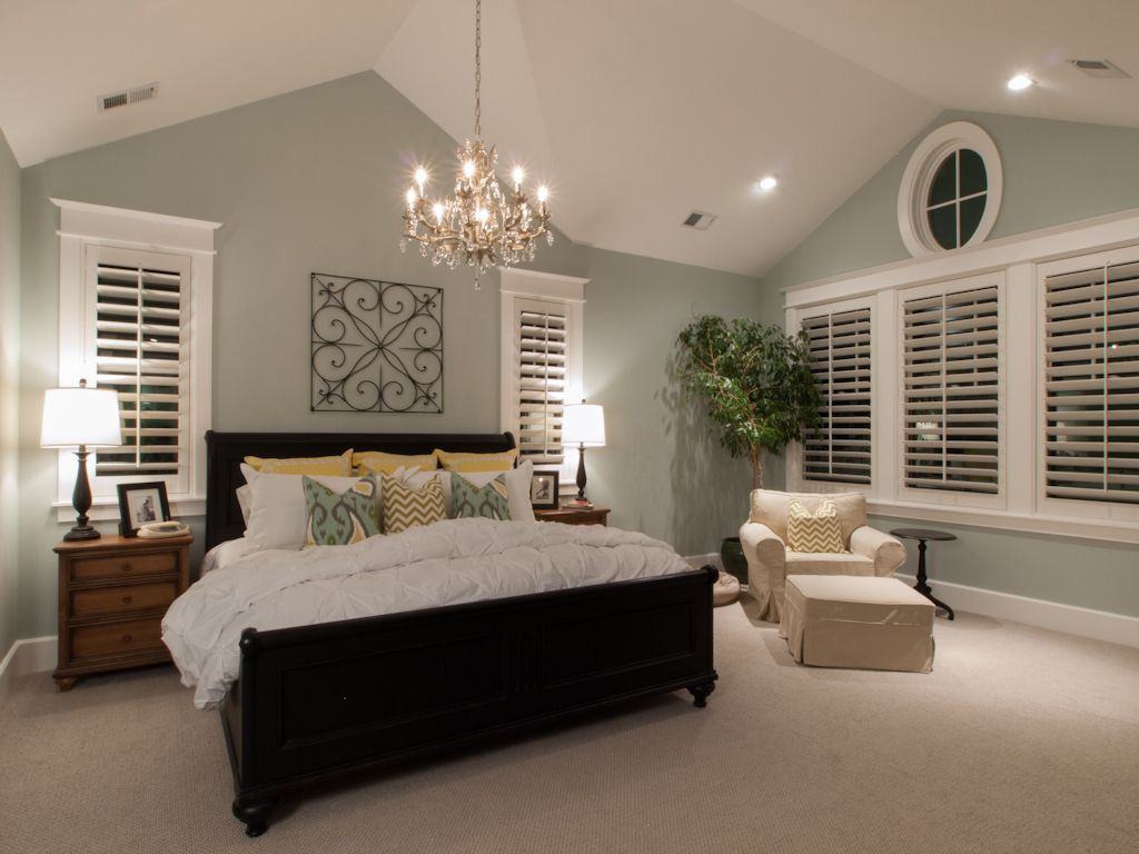 This large master suite features an intricate vaulted ceiling and nautical window house shit Master bedroom with sloped ceiling