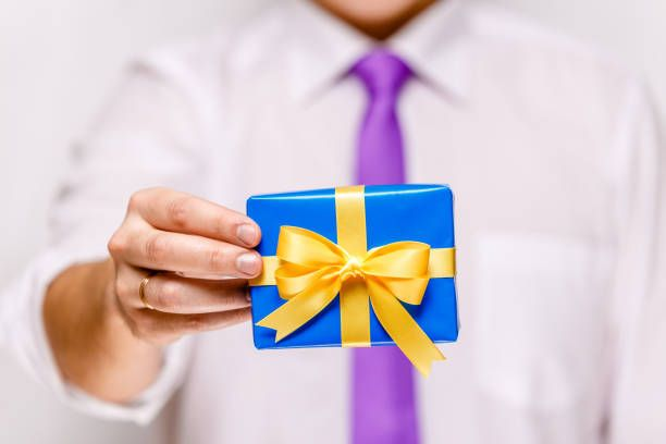 male hand holding a blue gift box with ribbon