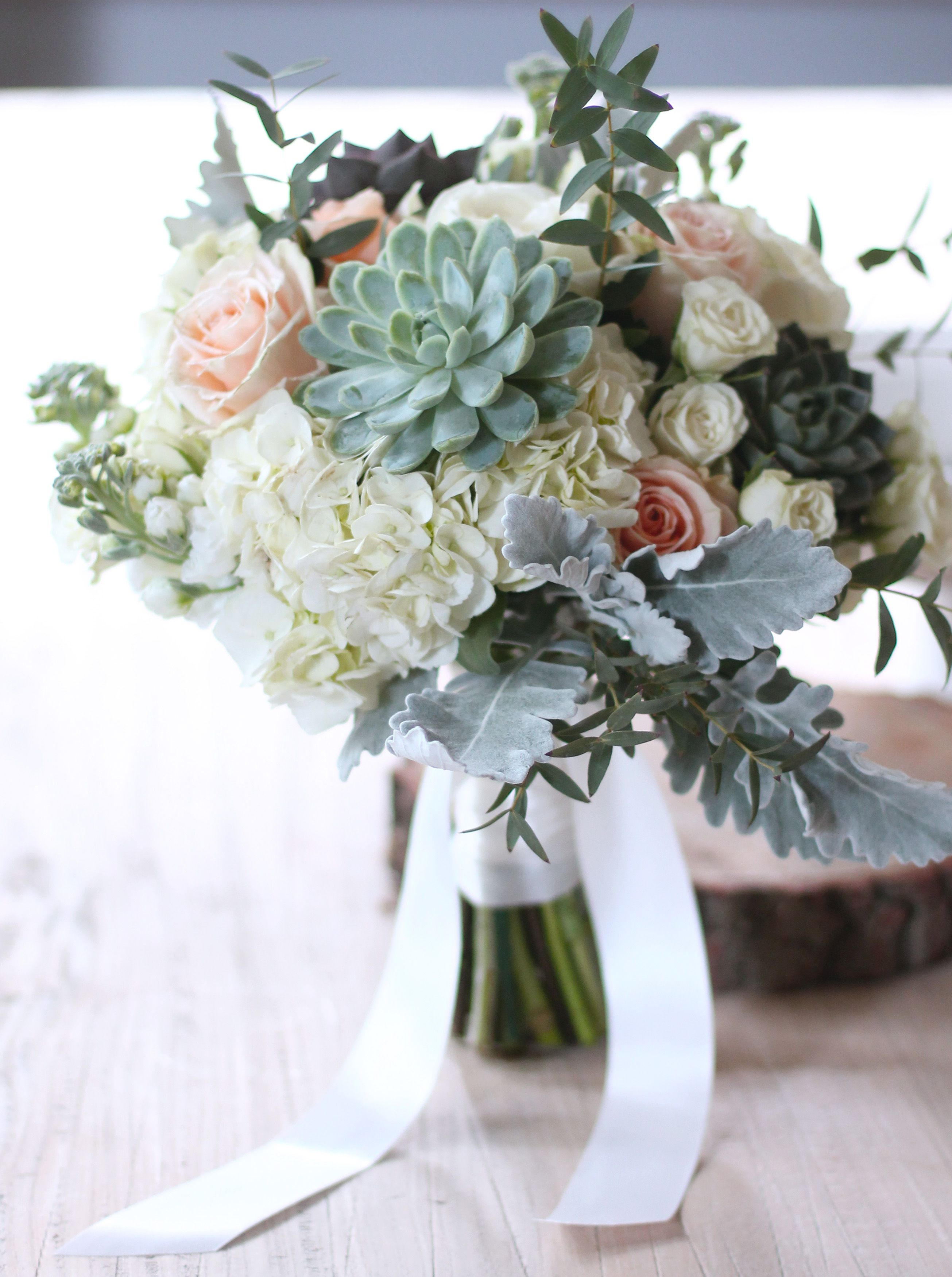 a bridal bouquet of succulents, hydrangea, roses, stock
