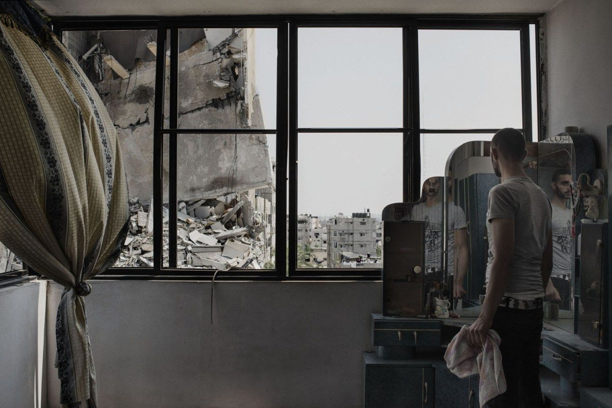 Jul. 20, 2014. A Palestinian man looks through the window of his house to buildings damaged by an overnight airstrike in Gaza City,
