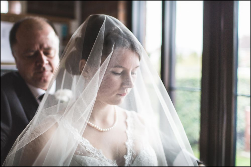 Father of bride helping with veil.