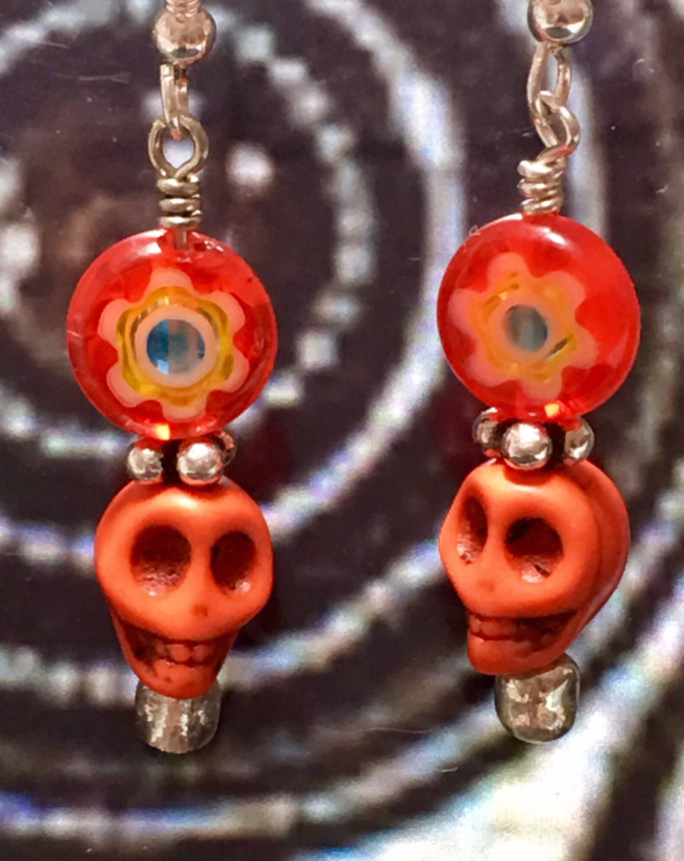 08b0a72ca Bright orange, turquoise, and yellow flower beads top funky dia de los  muertos skulls to create a festive pair of dangle earrings with silver  plated ...