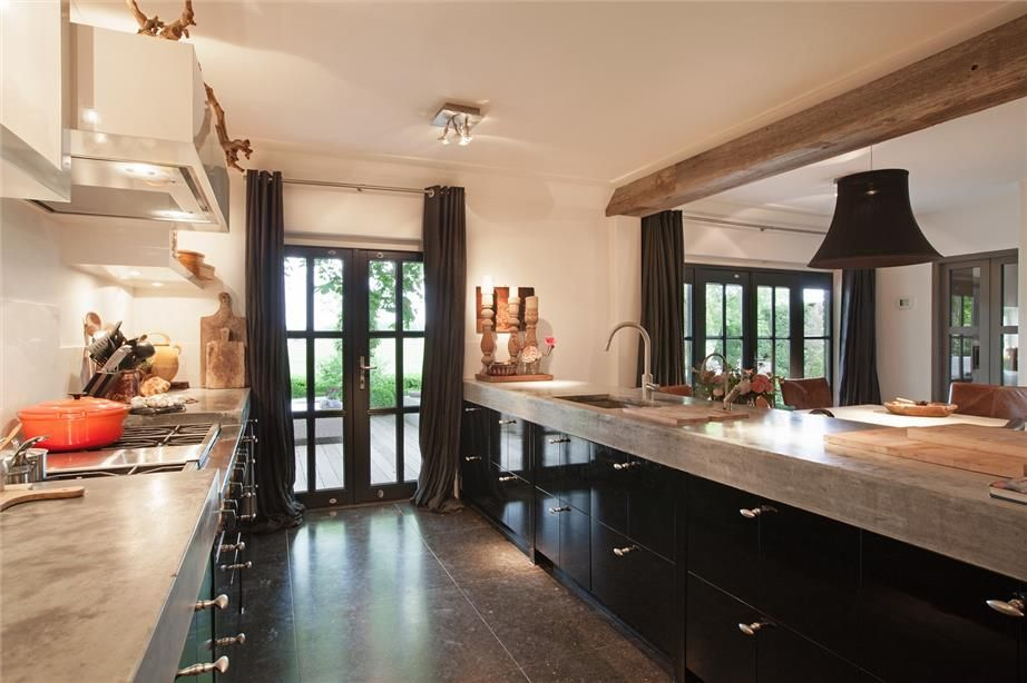 zwarte keuken maar dan met greeploze kasten en schuiven en betonnen bovenblad mooie zwarte ramen met zwarte gordijnen