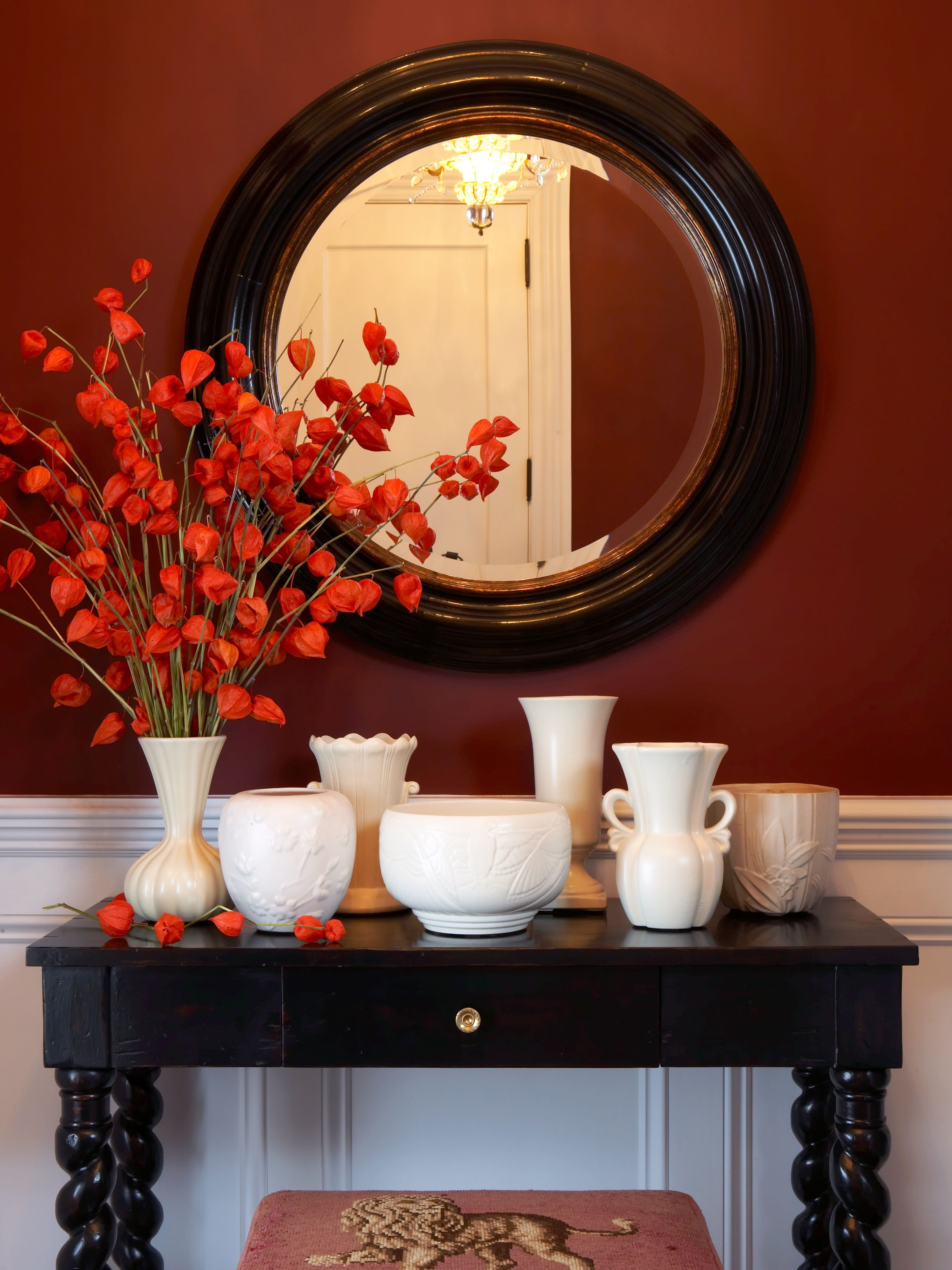 Transitional Entryway With Burgundy Walls, Orange Flowers, & White Accents