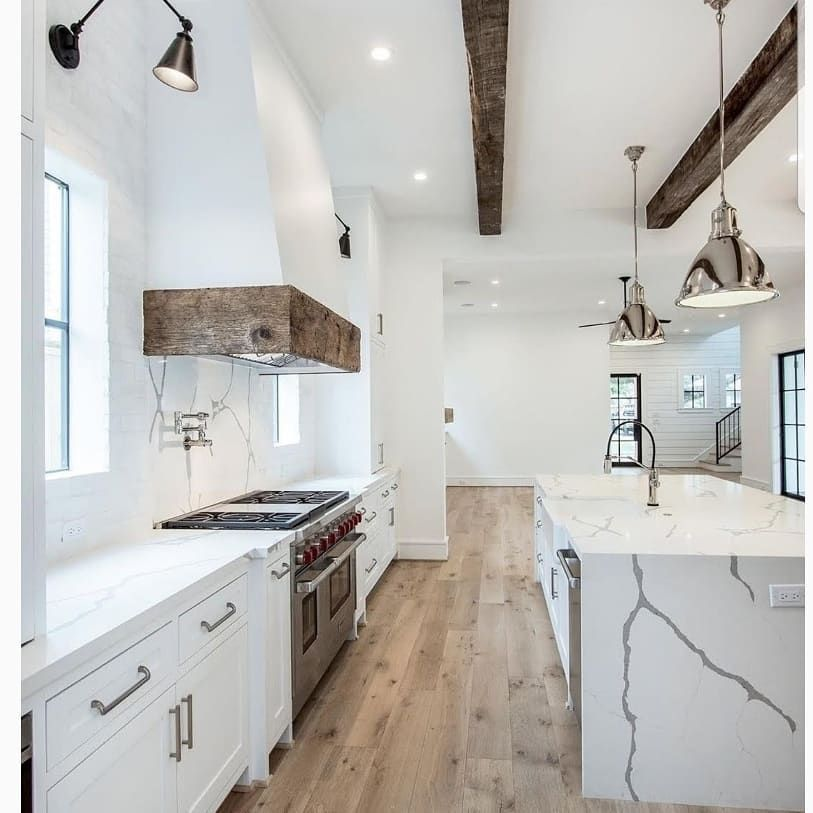 Gorgeous beams, you Always catch my eye!  But paired with this flooring selection...it sends me into a completely new level of adoration. This marble and polished nickel are the extras that put this over the top!  Gorgeousness, right?!  #kitchendesign #kitchenremodel #interiors #interiores #interiordesign #styleinspiration #kitchenislands #whitekitchen #modernfarmhouse #rustic #transitionalstyle #whitekitchen #whitekitchens #woodfloors #nickel #rangehood #dreamhome  #dreamhouse  #dreamkitchen