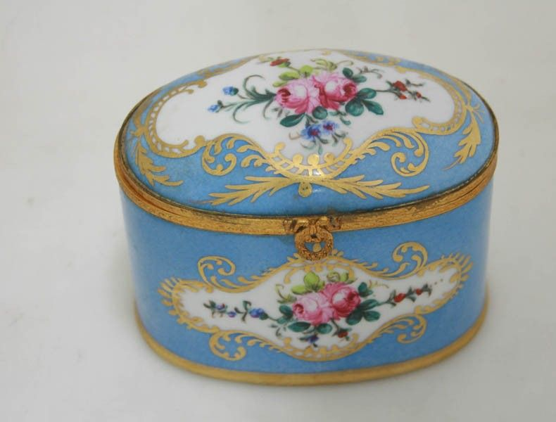 A French Sevres style bleu celeste jewel casket of oval form, the domed cover painted with a cartouche of garlands of flowers, with gilt highlights and ormolu banding. Signed 'Sehott.'