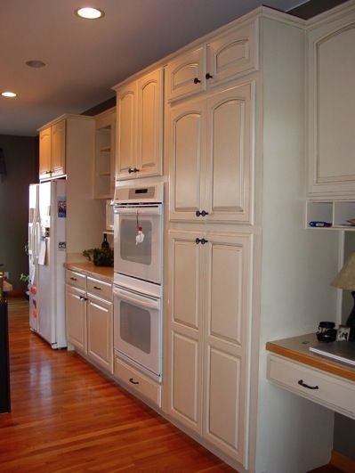 oak cabinets painted white with light glaze. with white appliances and  natural medium tone wood floor.