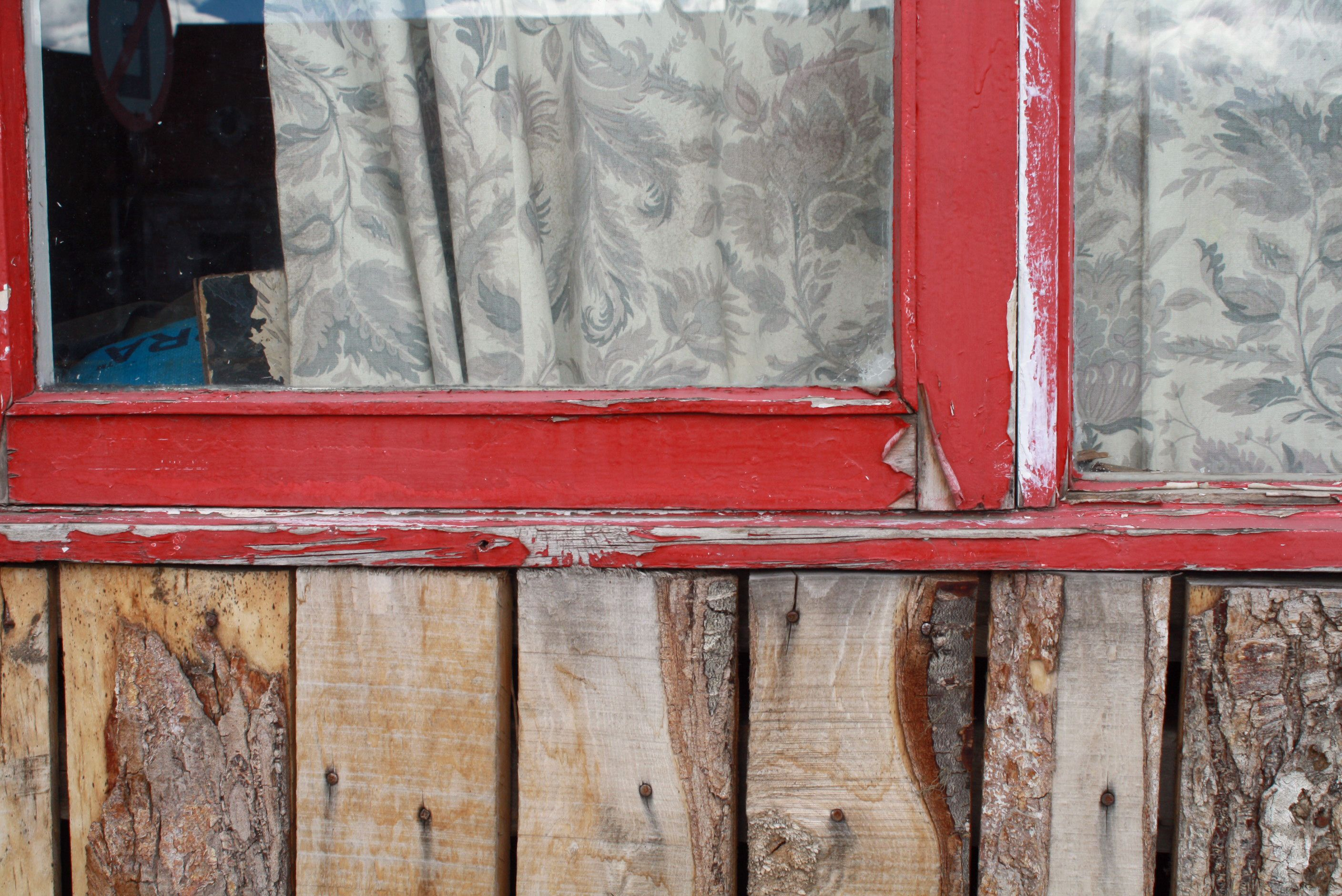 Red window with white curtains and wooden wall color splash