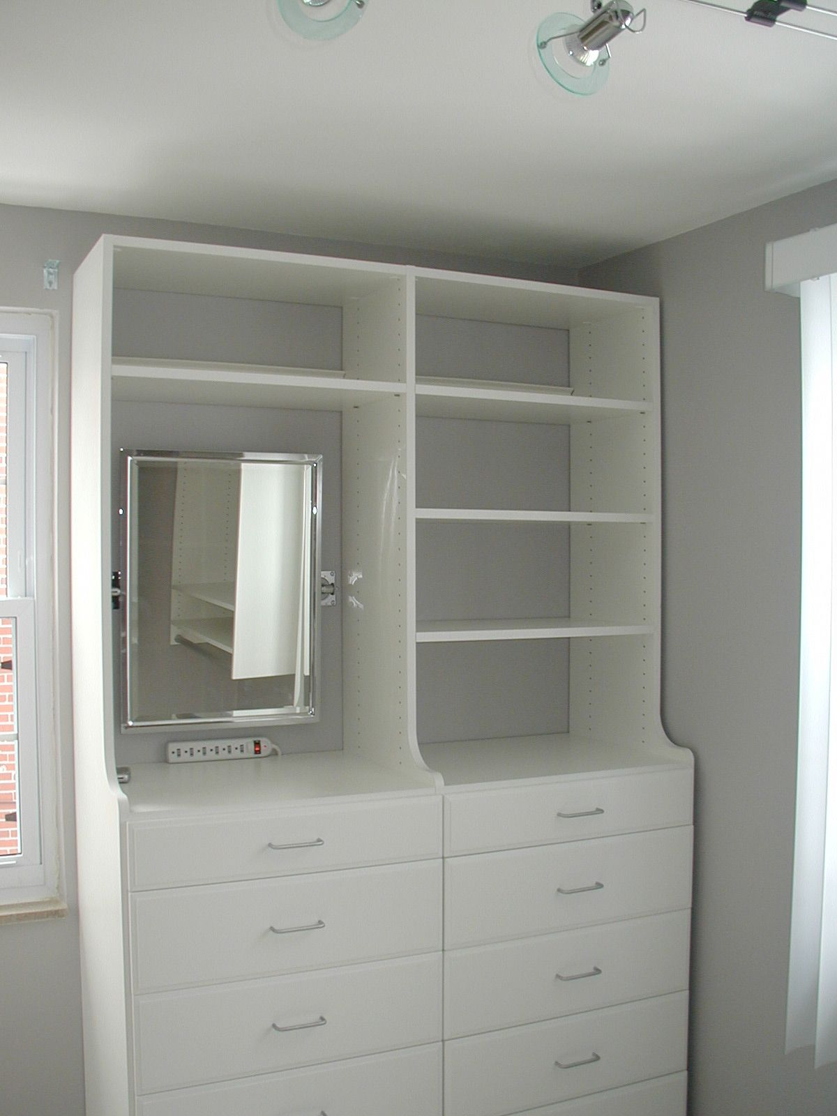 This client's walk in closet has two hutch units.  The drawers are 19 inches deep and the vertical side panels elegantly curve in so that the shelving above is 14 inches deep.  Tom also installed a vanity mirror and a power strip for our thrilled client.