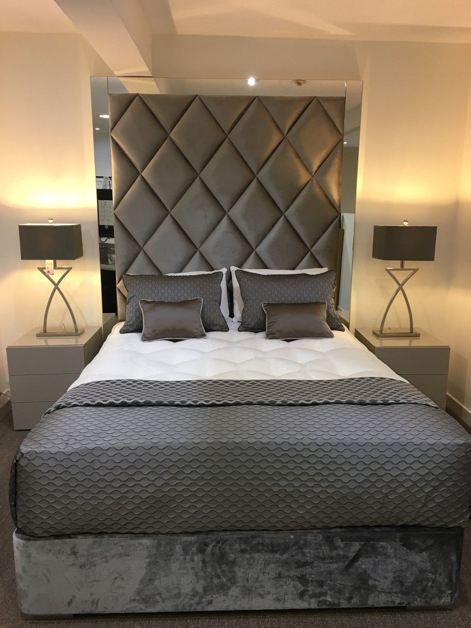 Upholstered headboard with mirrored surround on this