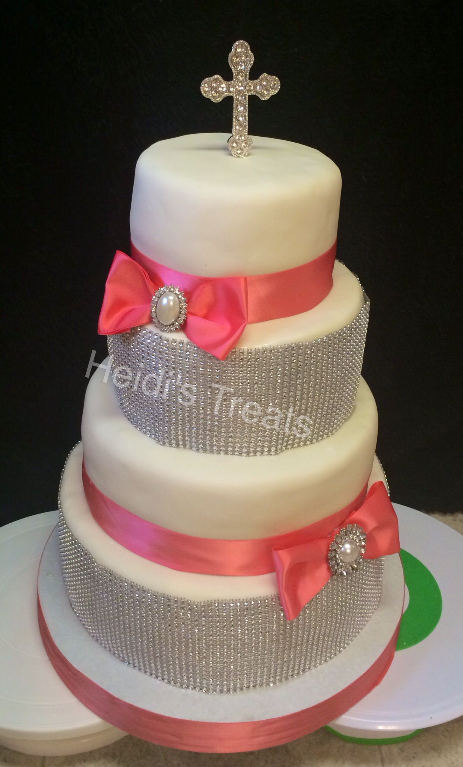 Bling and bow cake.  Coral colors and cross on top.
