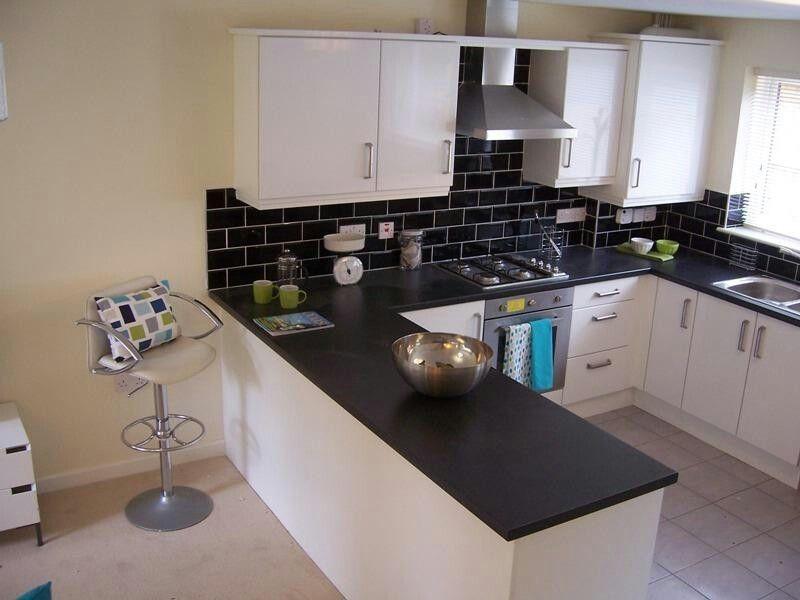 Paraschizzi nero e cucina bianca blu cucine