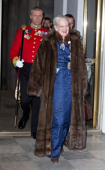 Queen Margrethe, dressed in a demure royal blue gown, with maroon embellishments decorating the neck and sleeves during a New Year's Levee held for Diplomats at Christiansborg Palace in Copenhagen, Denmark