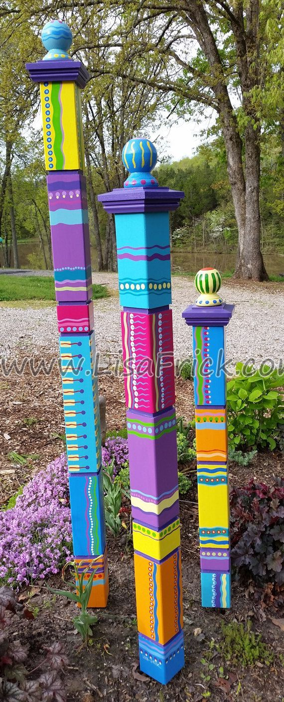 Garden Totem   Hand Painted Garden Art   Garden Sculpture   Sculptural Totems   Yard Art   Colorful Totems   Lawn Art is part of Garden art, Garden whimsy, Garden totem, Garden poles, Garden projects, Colorful garden - ATTENTION!  PLEASE READ ENTIRE DESCRIPTION   Please be patient with me as I slowly find time in my studio again   I am the sole caregiver for my husband who suffered a ruptured brain aneurysm last summer   These are all individually made and hand painted by me   Craftsmanship takes time, but it's worth it!  I realize the ship time on these is long, but I will ship earlier if I can   I have it listed long to give me plenty of time to do a quality job while also caring for my husband   FREE SHIPPING!!! If you purchase a set of 3 totems, enter the code  3TOTEMS  to receive a $50 00 discount  (This discount only applies if you order a set of 3 totems   It does not apply to the purchase of a single totem)  Totems are made to order, I can generally have them ready for delivery in 48 weeks  Two color schemes are available, the  Earthy  color scheme which consists of mustard yellow, burnt orange, brick red, dusty blue, plum, etc , and the  Bright  color scheme consists of vivid shades of lemon yellow, tangerine orange, lime green, magenta, turquoise, etc    My garden totems are hand painted on 4  x 4  Western Cedar  They are not the mass produced vinyl wrap on a PVC plastic pole   Each one is different, each one is unique, how ever they will look very similar to the ones pictured  They add a great splash of color to your garden either as an accent or the centerpiece   They are protected with a UV protecting marine varnish to help prevent fading and to ensure a long life   However to prolong their vivid color, I recommend placing them in a shaded area and that you store them indoors in the winter months when the sun is at it's harshest    The Mini Totem Measures  32  from the base to the top of the ball  The Small Totem Measures 41 inches from base to top of the ball The Medium Totem measures 54 inches from base to the top of the ball    The Large Totem measures 65 inches from base to the top of the ball Each Totem comes with a piece of rebar that is to be driven into the ground, leaving 10  above ground   Each Totem is drilled 1012  deep into the base to then slide over the exposed rebar   You can then push and pull to get them  plumb   The only tools you will need to install are a heavy hammer to drive the rebar into the ground and a level would be handy for plumbing it up  Have a specific color scheme in mind  I currently offer 2 standard color schemes the original Bright colors and now the Earthy color scheme for a more muted natural look   But I'm open to custom colors if you have an idea of your own  Give me a shout, I'm sure I can make something special for your garden  If purchasing a set of all 3 totems, enter the code  3TOTEMS  to receive a $50 00 discount