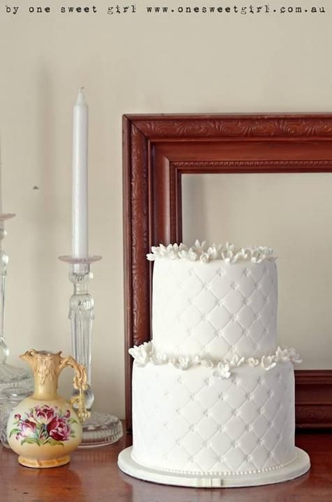 simple, white, quilted cake decorated with tiny white flowers