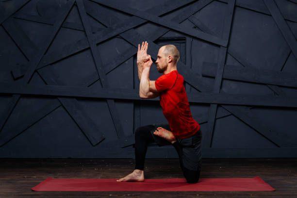 man practicing advanced yoga against a urban background