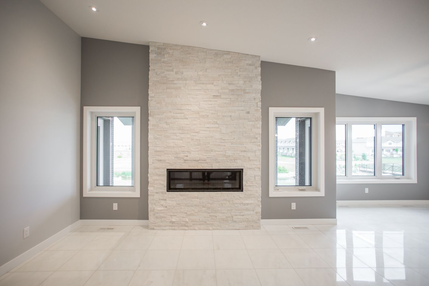 Clean Looking Fireplace With White Stone From Floor To Ceiling