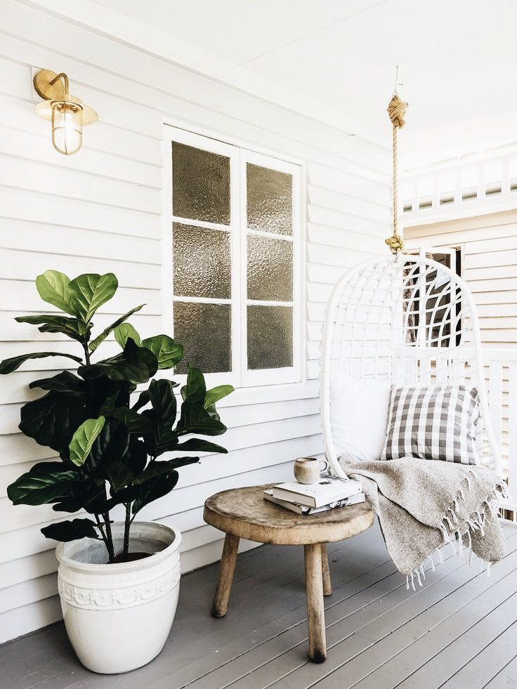 white farmhouse porch, white porch swing, fig leaf plant, wood outdoor side table, gold light fixtures, gray porch