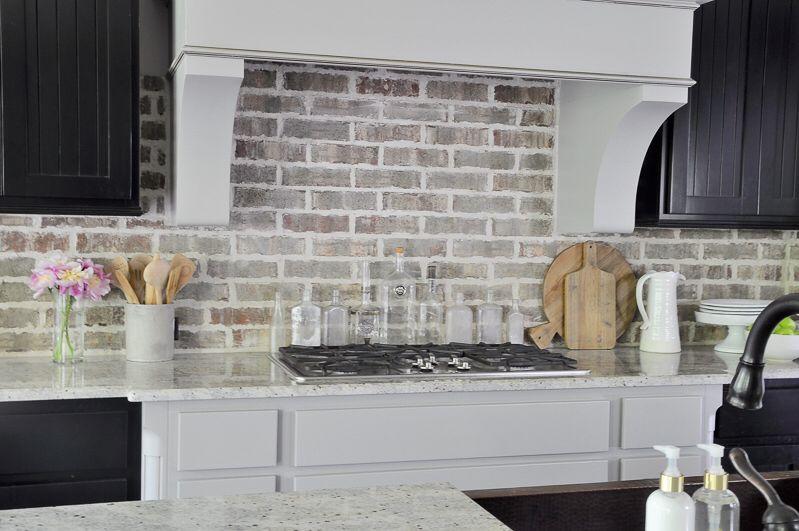 gorgeous kitchen with brick backsplash large vent hood and black cabinets
