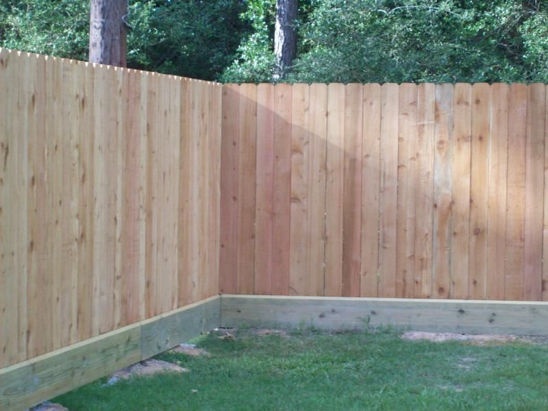 the use of a rot board along the bottom of a standard wood privacy fence can