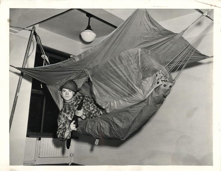 Medium image of soldier levels a tommy gun as he swings in the new jungle hammock on display at the army quartermaster branch procurement office fifth avenue