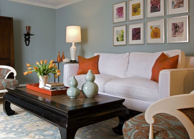 Blue Wall Orange Accent Pillows And White Sofa Chair For The Living Room