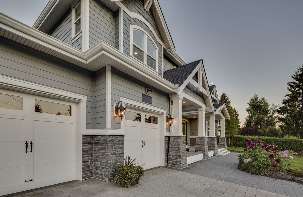 Grey Siding, Stone Siding, White Garage Doors With Windows, Landscaping,  Two