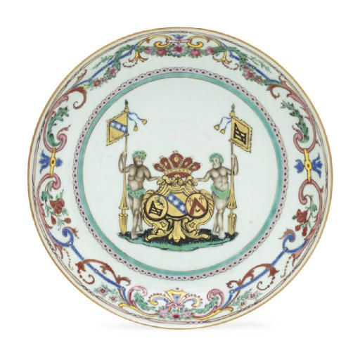 A LARGE BELGIAN MARKET FAMILLE ROSE ARMORIAL SAUCER DISH  MID 18TH CENTURY  The center with a large coat-of-arms of Goos, Vecquermans and Golbeau flanked by wild man supporters bearing gilt pennants, all supported on a grassy mound and within gilt and sea-green borders on the well, the rim brightly enamelled with colorful Berainesque scrollwork entwined with a garland of blossoming vine  10 in. (25.4 cm.) diameter