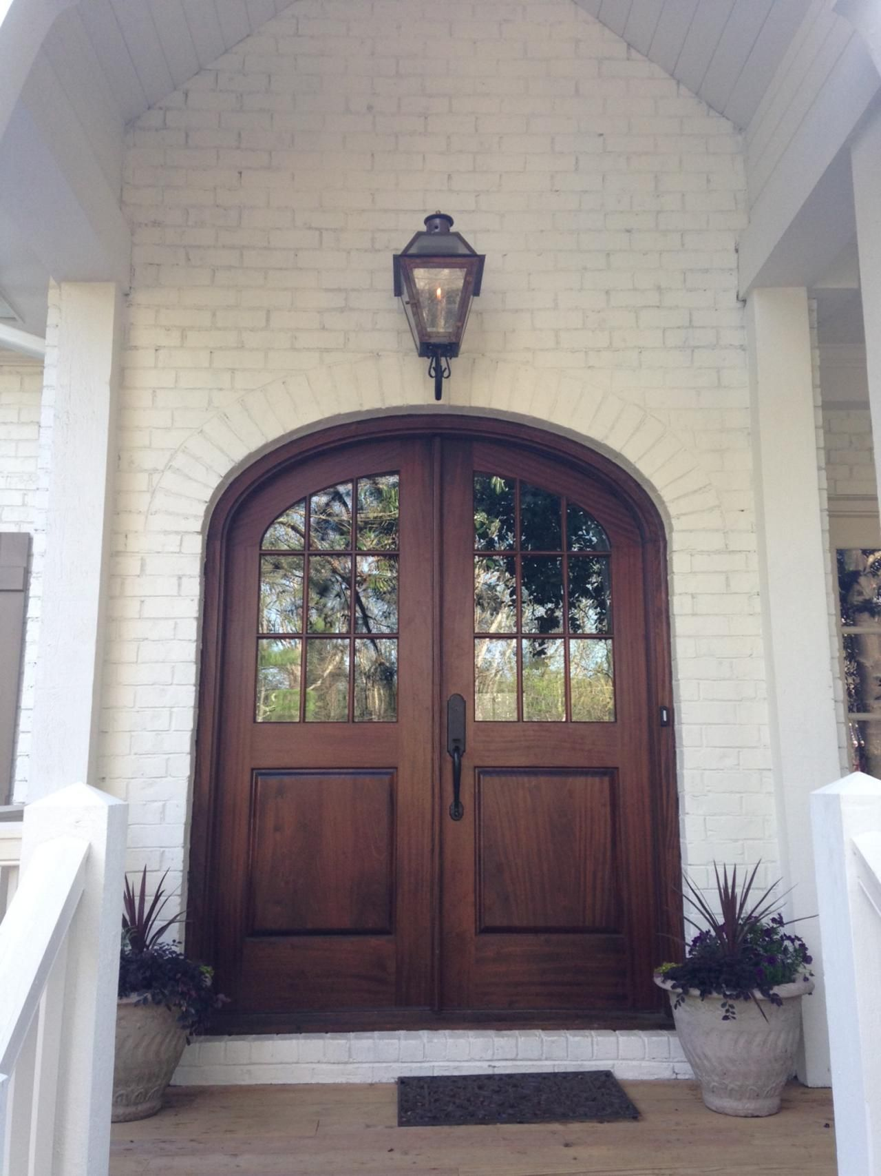 Brown arched glass front door on white brick home build for Front door arch design