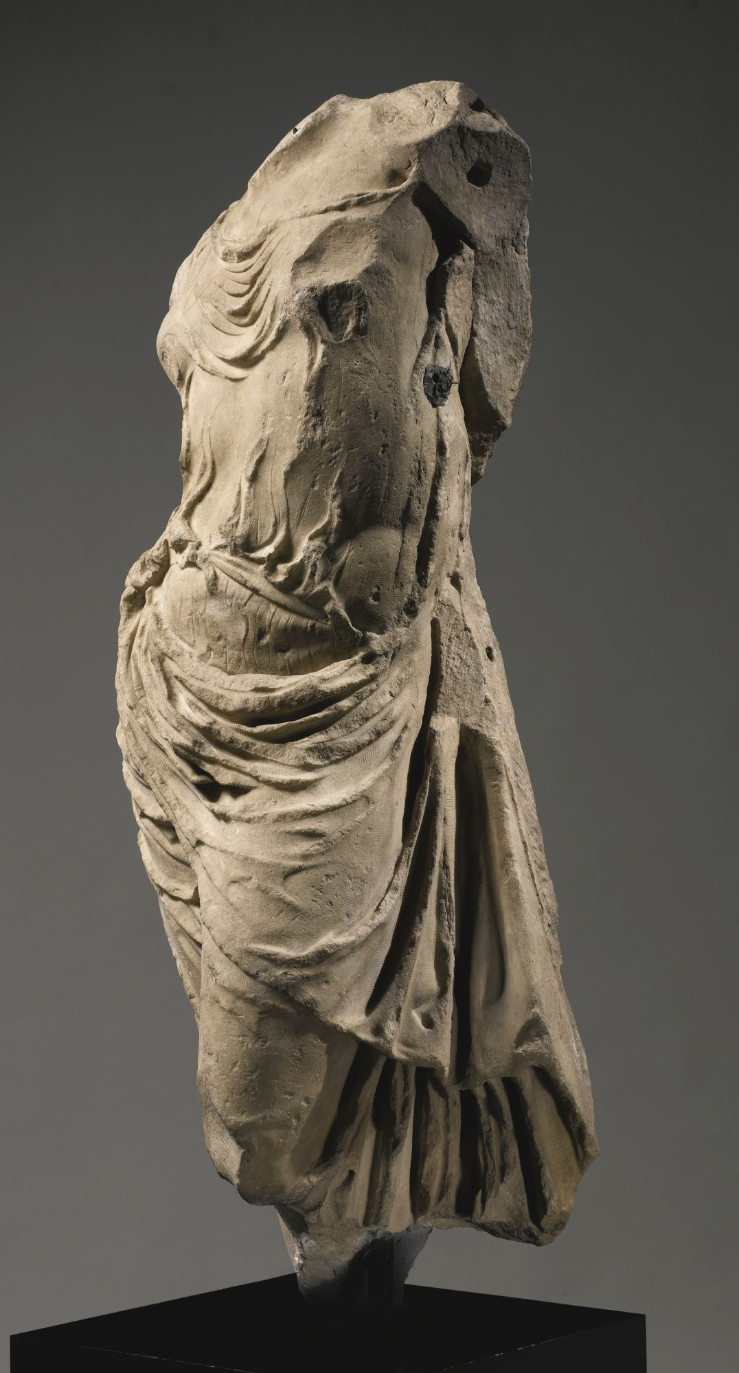 """""""wearing a diaphanous chiton with buttoned sleeve, narrow belt tied at the waist, and himation with long deeply carved folds falling at her side, some gathered up against the edge of the chiton in back"""" a hellenistic marble tor 