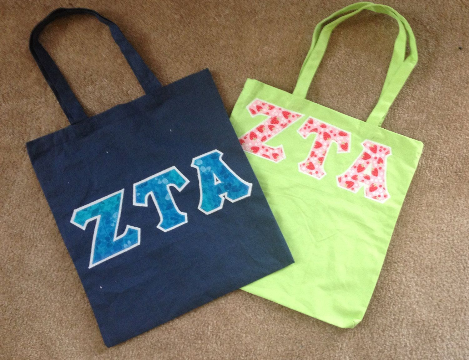 Greek Lettered Tote bags. $10.00.           10 different colors, 100's of fabrics to choose from.        Licensed for:  Alpha Chi Omega,  Alpha Delta Pi,  Alpha Omicron Pi,  Alpha Phi,  Alpha Xi Delta,  Chi Omega,  Delta Delta Delta,  Delta Gamma,  Delta Zeta,  Kappa Delta,  Kappa Kappa Gamma,  Phi Mu,  Sigma Kappa, and  Zeta Tau Alpha