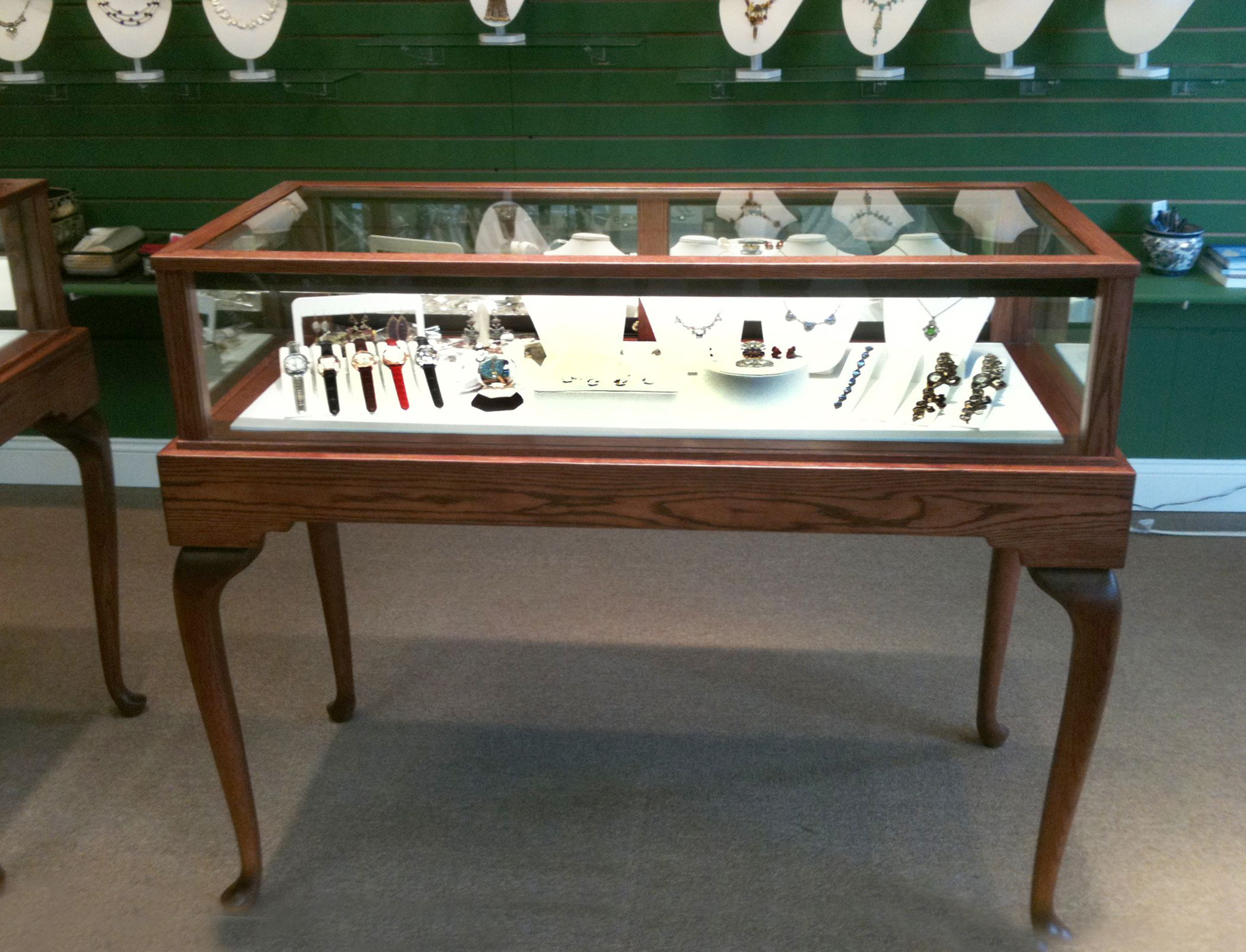 """The display cases are beautiful! We love the cordovon cherry stain on red oak with the white leatherette deck pad. Here are a couple of photos of the units."" -- Canary International, Inc., Farmington, MI   -   Gloria Hsu, Partner   5/1/2012."