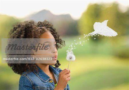 African girl blowing dandelion, seeds turning into bird