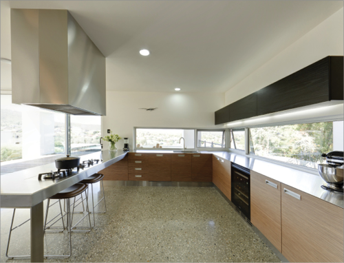 The Kitchen Of A House Has Low Windows On One Side, And Ceiling Length