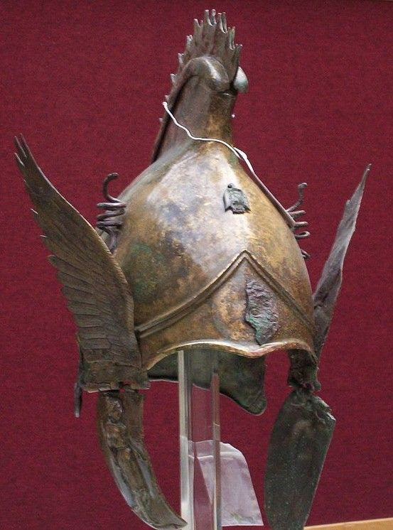 Greek bronze winged helmet of PHRYGIAN-CHALCIDIAN type, 4th cent. BCE. The crown has a raised peak surmounted by a spiked crest, a palmette in relief at the back bordered by spiral tendrils, a tendril spiraling out to each side surmounted by lotus blossoms, the neck-guard with a separately-made protective edge with volutes at each end, plume holders in the form of coiled snakes on either side of the central crest. See image 2 for further description.