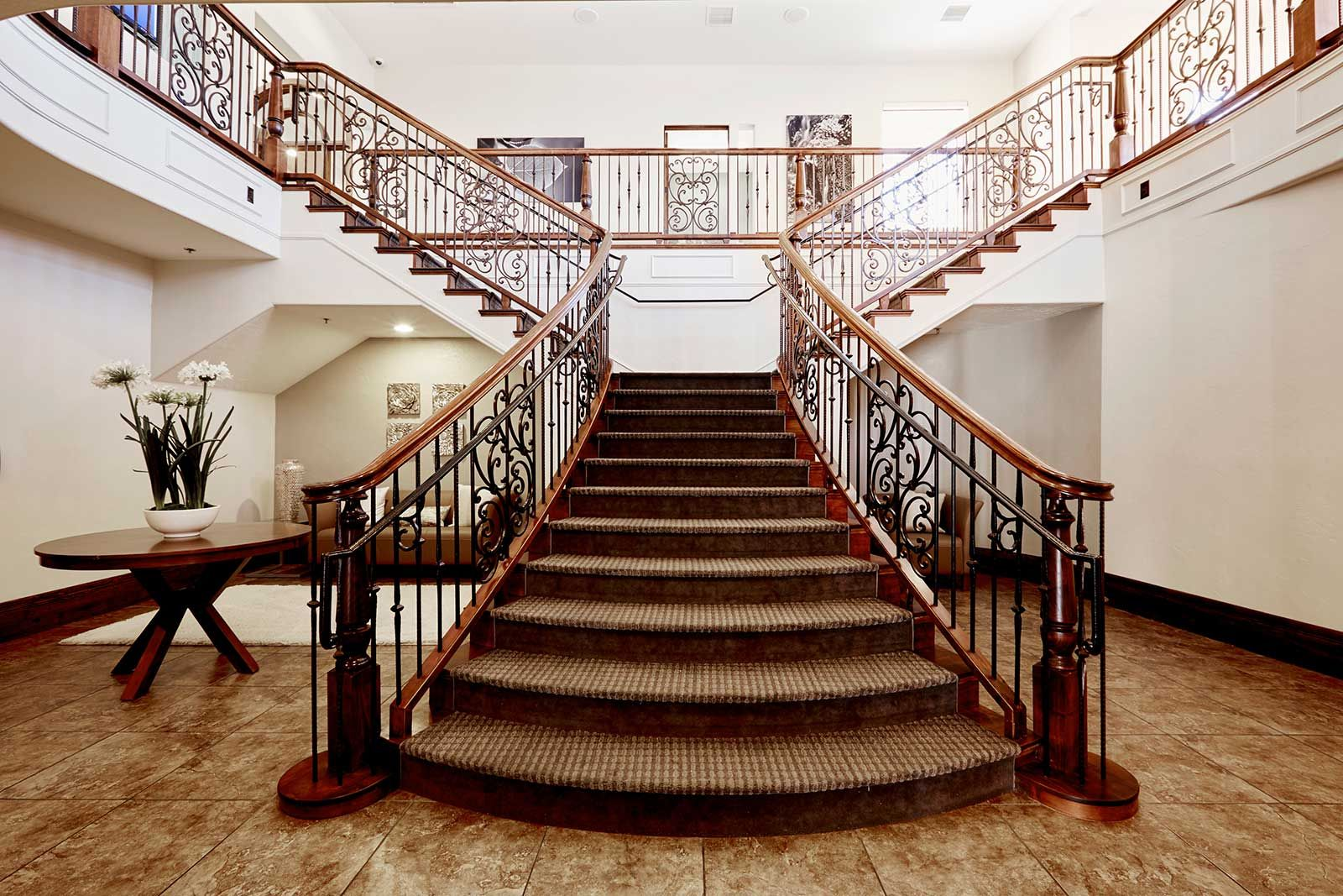 Rod Iron Rails Truly Make This Bifurcated Stair Case Stand Out