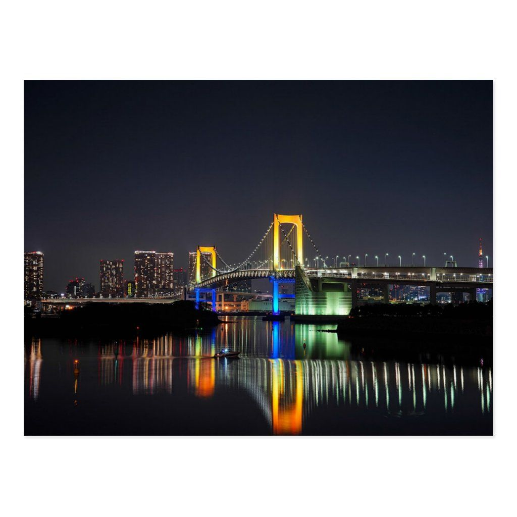 Night view of the colorful Rainbow Bridge (lit with yellow, blue, and green lights) located in Minato, Tokyo, Japan. It is a suspension bridge that connects Tokyo with the man-made island of Odaiba. The lights, which are powered by solar energy, change seasonally for special occasions. The rainbow colors appear during the holiday season. Photo by Luke Ma