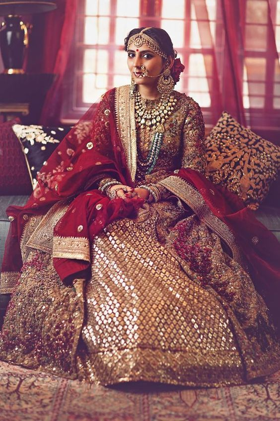 Damn! We have no words! This stunning Sabyasachi bride is just crazy beautiful! This red and gold lehenga, this dupatta, that jewellery and those flowers in her hair! | #IndianWedding #bridalStyle Curated by #WittyVows - The ultimate guide for the Indian Bride | www.wittyvows.com
